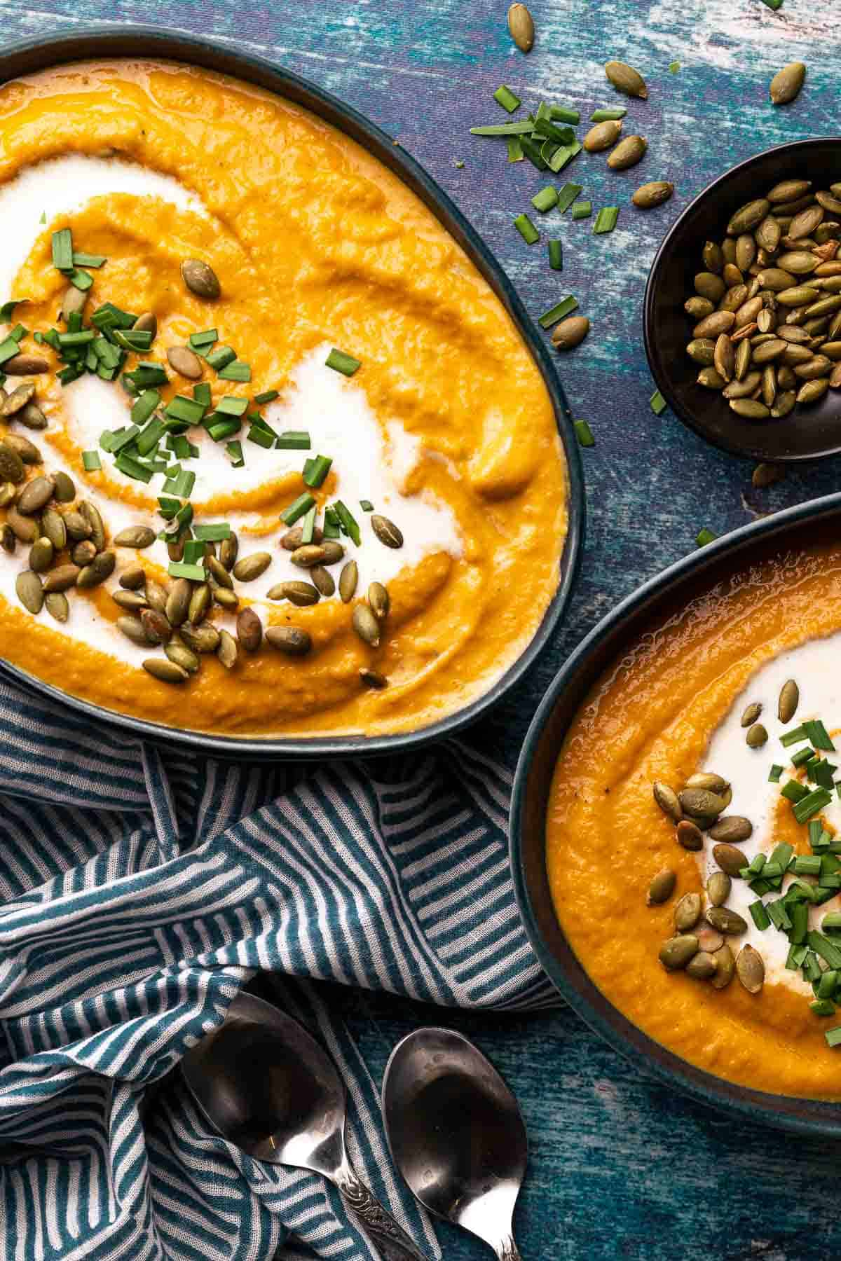 two bowls of pumpkin sweet potato soup with herb and pumpkin seed garnish and bowl of pumpkin seeds on the side