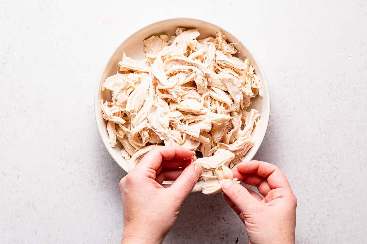 hands shredding chicken breast over bowl