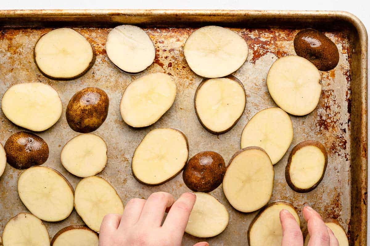 hands spreading potato slices out on baking sheet