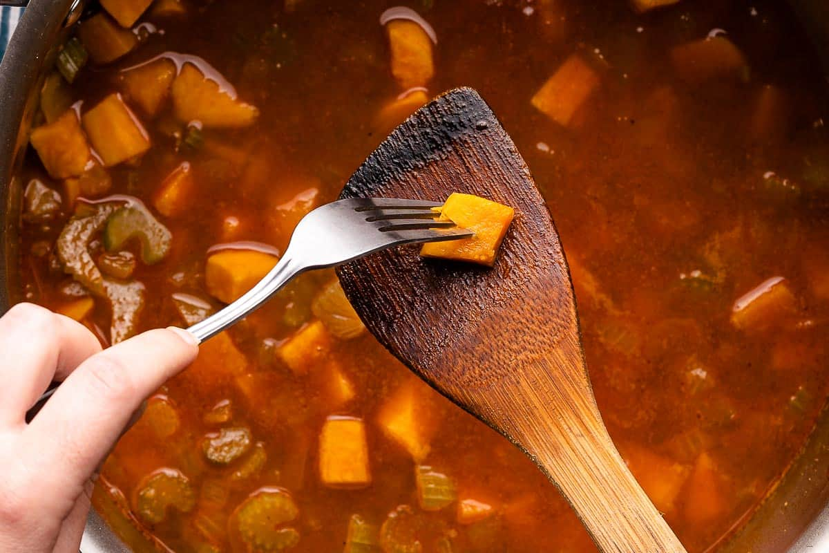spoon holding piece of sweet potato with fork piercing the piece