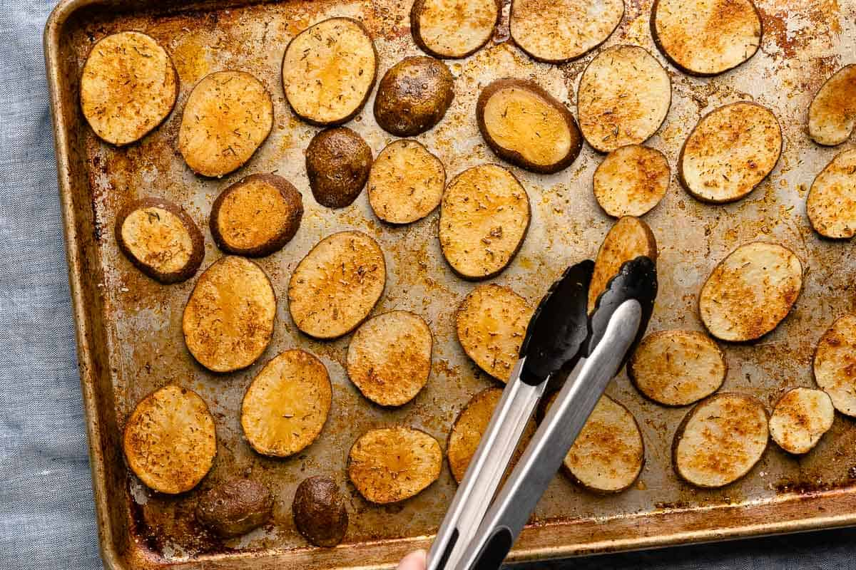 tongs turning half cooked potatoes over on baking sheet