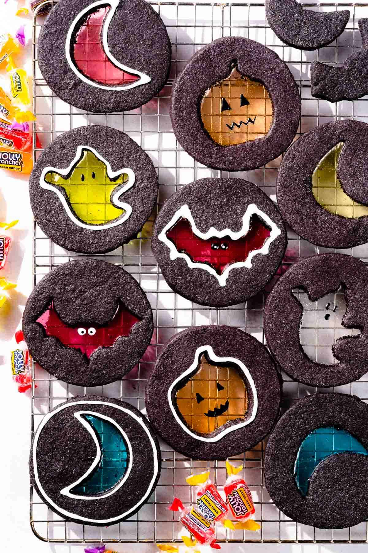 Halloween windowpane cookies on cooling rack with candies on the side