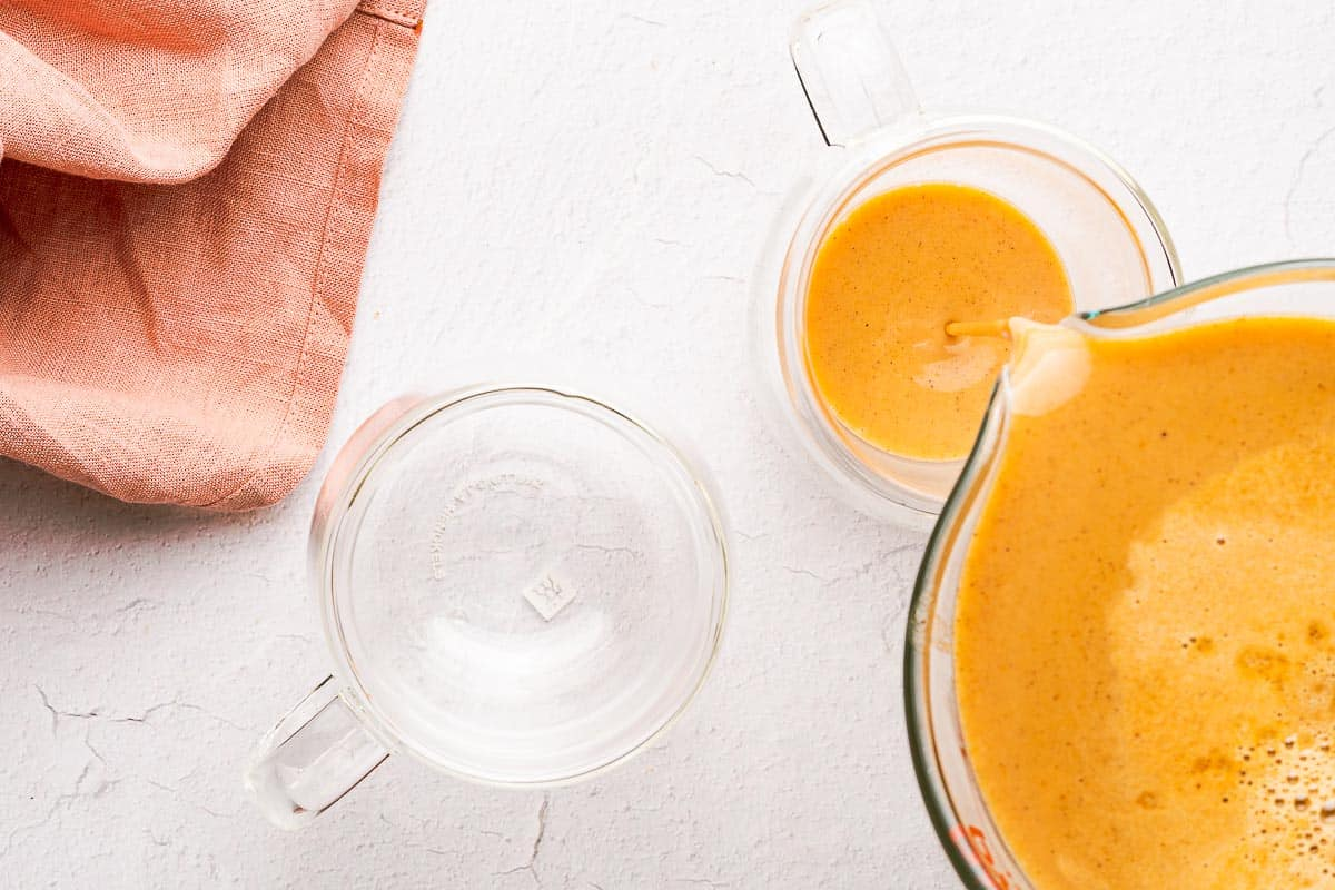 pumpkin spice syrup being poured into glass mug with empty mug on the side