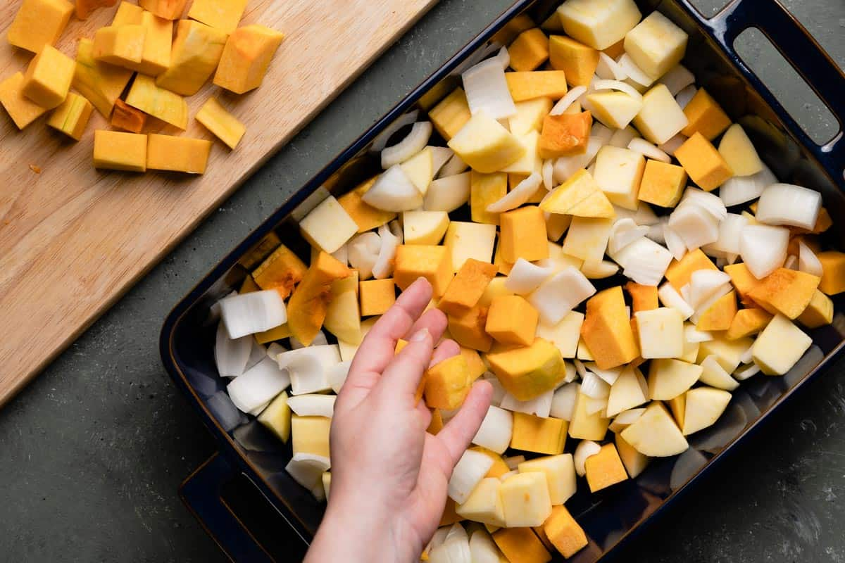 hand adding a few chunks of butternut squash to pan with chunks of apples onions and butternut squash
