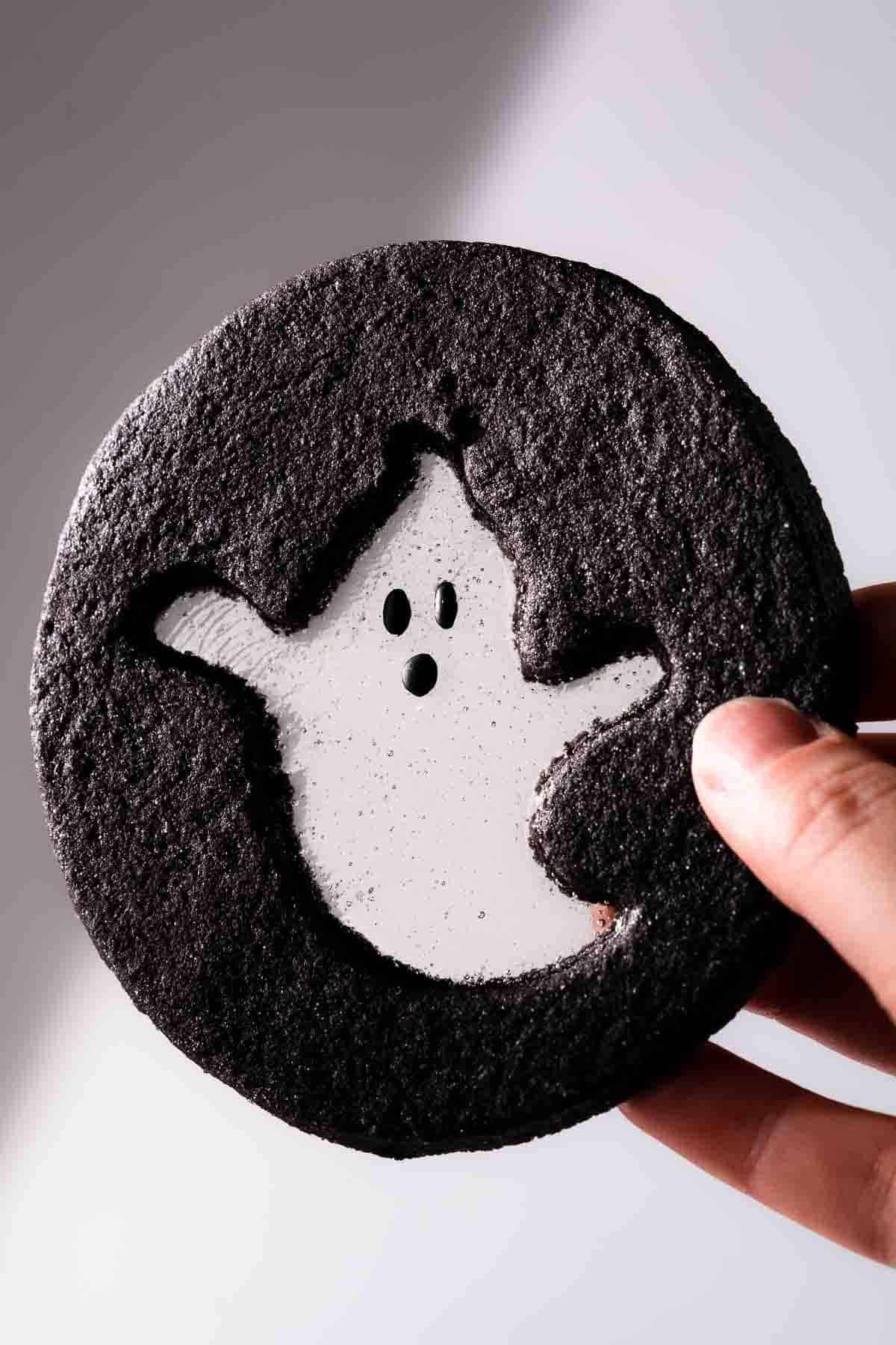 Halloween windowpane cookie with ghost design held in hand