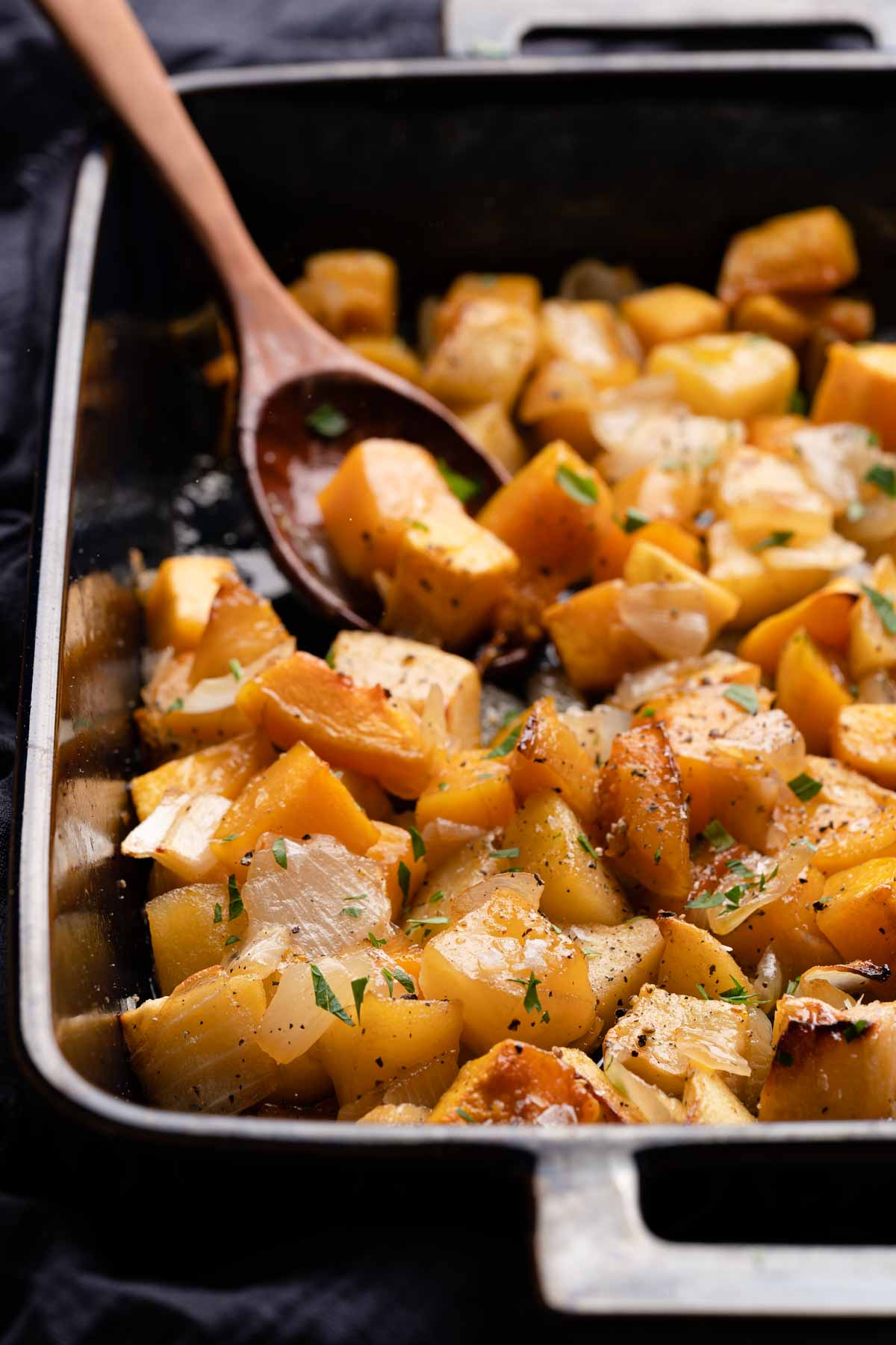 maple glazed squash and apples in casserole dish with wooden spoon