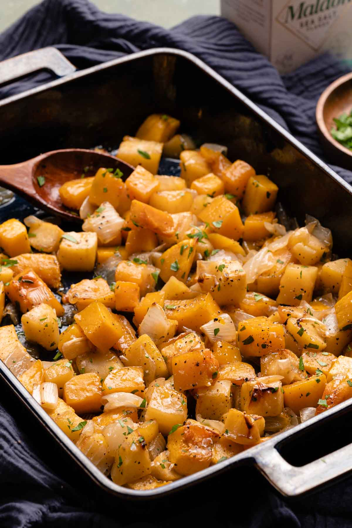 squash and apples in blue casserole dish with herbs on the side