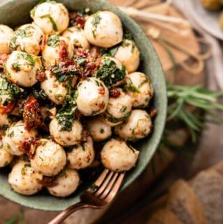 marinated mozzarella balls in bowl with fork