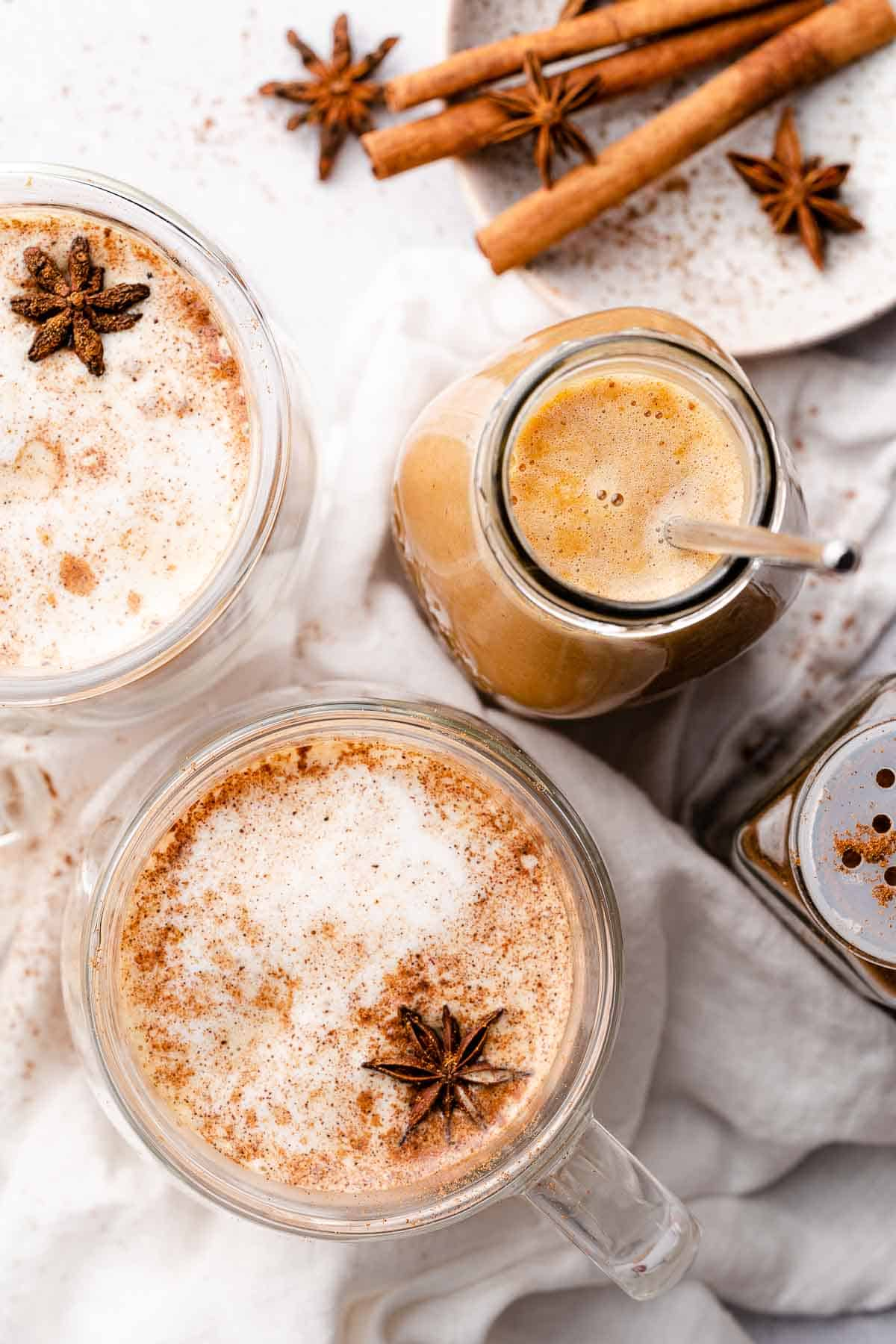 pumpkin spice syrup in glass jar with two lattes and spices on the side