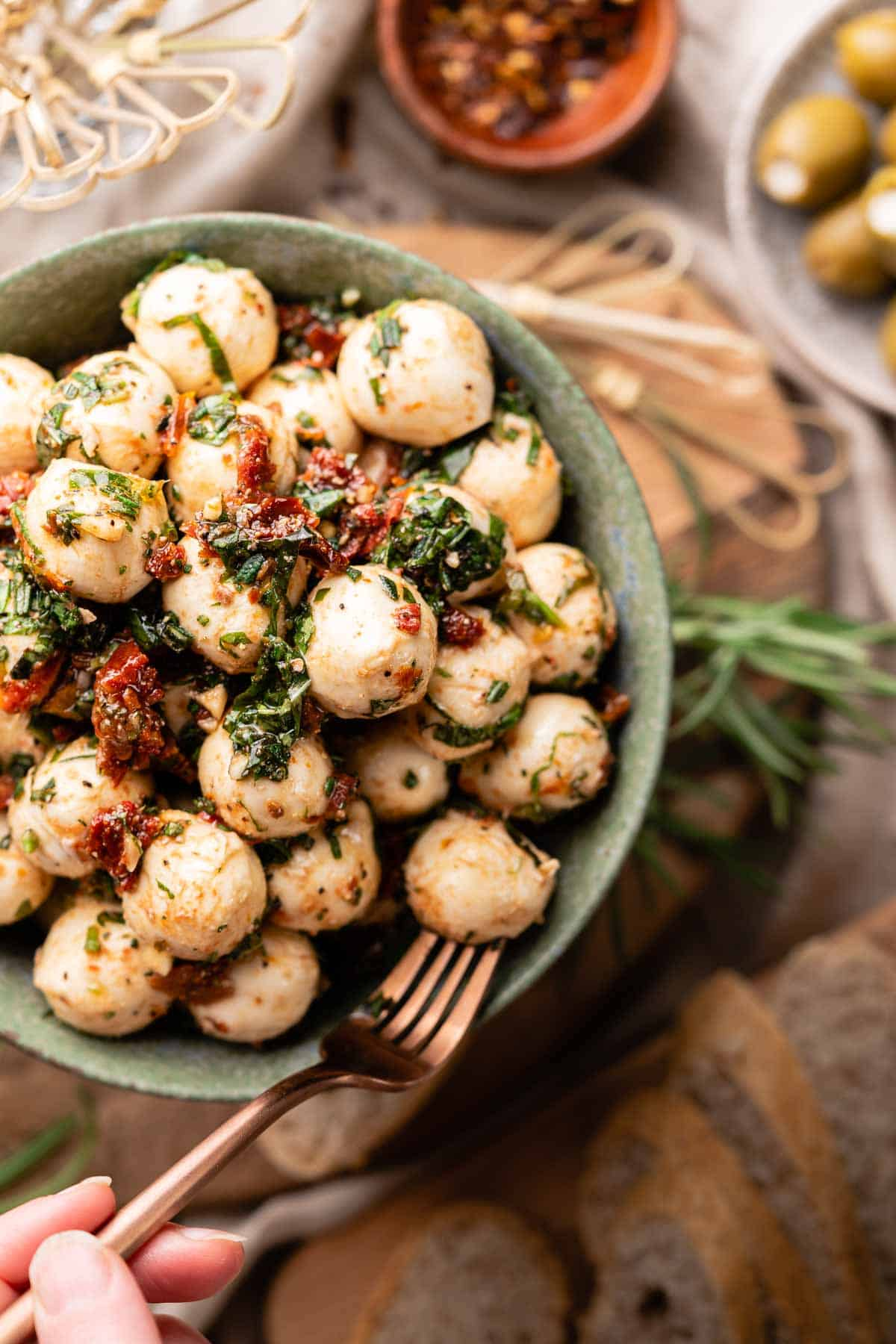 marinated mozzarella balls in green bowl with fork serving one piece