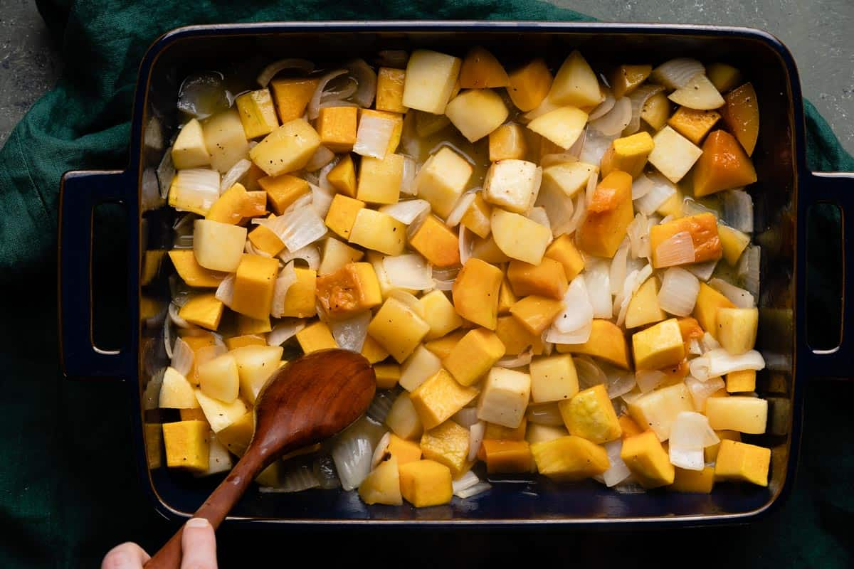 pan of half cooked butternut squash and apples with wooden spoon stirring them