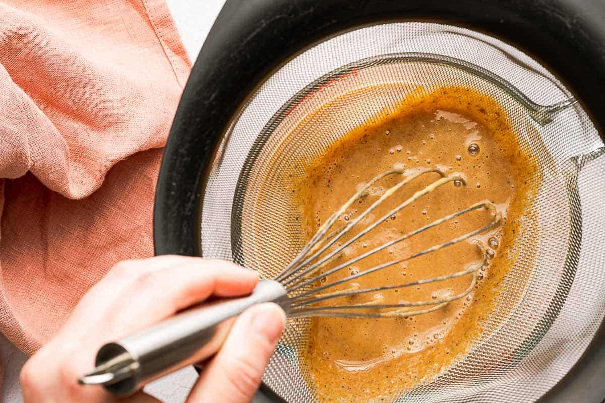 pumpkin spice syrup being strained with fine mesh sieve and whisk pushing syrup through
